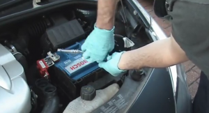 mechanic replacing corrosive battery